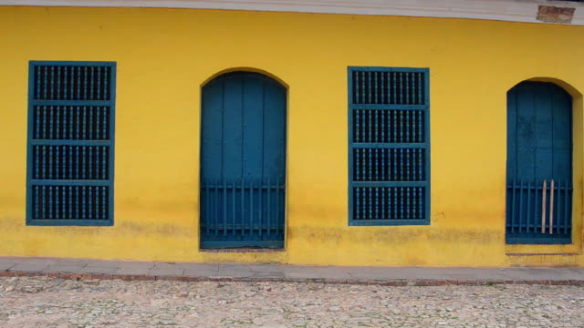 ms shot of trinidad cuba street with cuban local bicyclist yellow building in old colonial plaza / trinidad, cuba - caribbean stock videos and b-roll footage