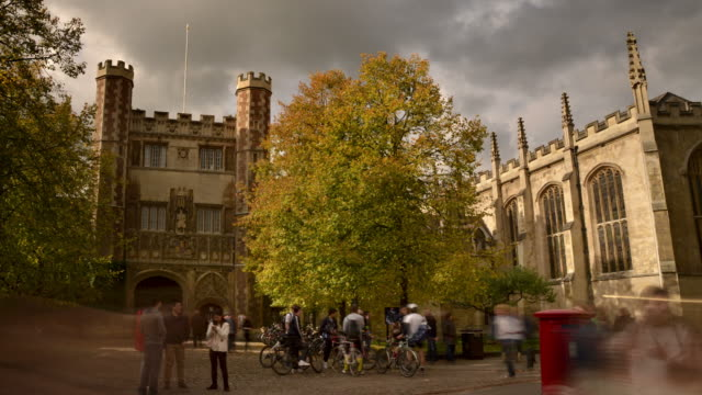 ms t/l shot of trinity college cambridge sunny autumn day passing fluffy clouds locals tourist and students passing with dramatic changing light / london, greater london, united kingdom - cambridge university stock videos and b-roll footage