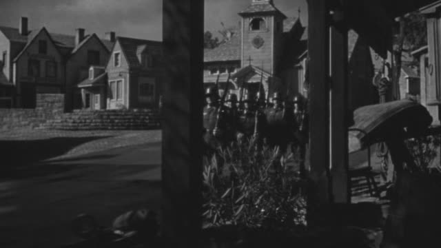 MS Shot of Troop moving in front of houses