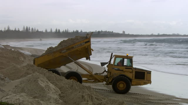 MS PAN Shot of Truck dumping sand on beach and compound / Kingscliff, New South Wales, Australia