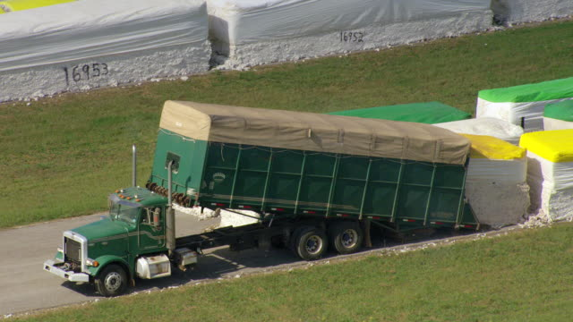 vídeos y material grabado en eventos de stock de ms aerial zo shot of truck dumps cotton bales in row on field in lawrence county / alabama, united states - cotton