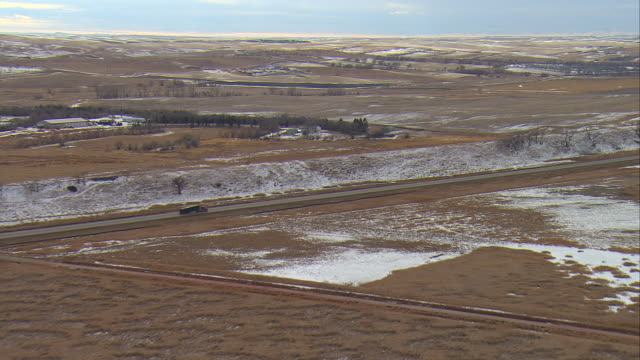 WS AERIAL Shot of truck hauling pipe on highway 200 at Bakken oil field near Watford City / Watford City, North Dakota, United States