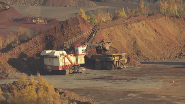 vidéos et rushes de ms aerial shot of trucks and other equipment moving ore from piles at hull rust mahoning mine / hibbing, minnesota, united states - industrie minière