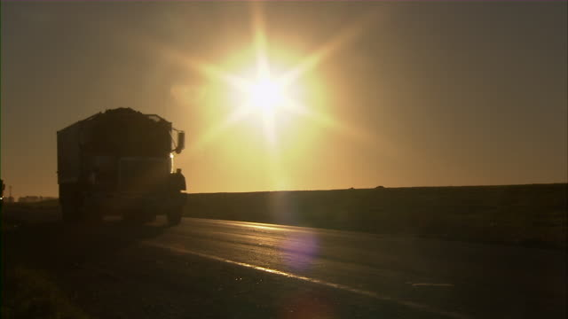 shot of trucks carrying sugar beets and passing by on a highway in the early morning. - comfort food stock videos & royalty-free footage