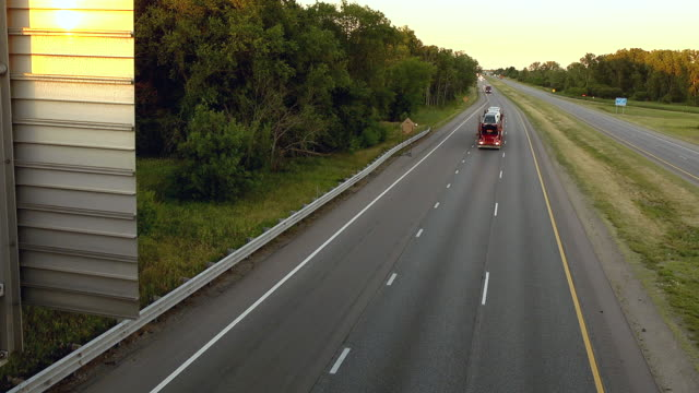 MS Shot of trucks hauling new automobiles on an interstate highway / Chelsea, Michigan, United States