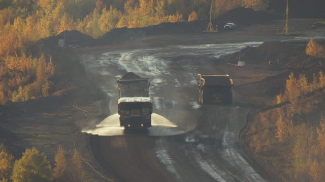 CU AERIAL Shot of trucks spraying roads with water at Hull Rust Mahoning Mine / Hibbing, Minnesota, United States