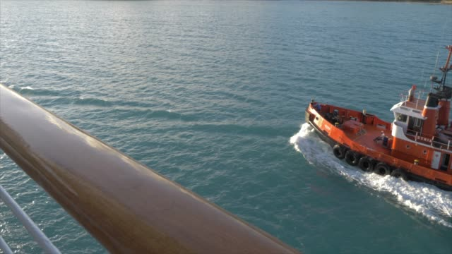 vidéos et rushes de shot of tug boat guiding cruise ship into st. john's from moving cruise ship, antigua, antigua and barbuda, caribbean sea, west indies, caribbean, central america - remorqueur