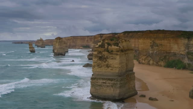 ws pan t/l shot of twelve apostles battered by waves and stormy clouds billowing / port campbell, victoria, australia - naturwunder stock-videos und b-roll-filmmaterial