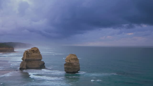 ws pan t/l shot of twelve apostles battered by waves and stormy clouds billowing / port campbell, victoria, australia - zeitraffer tag bis dämmerung stock-videos und b-roll-filmmaterial
