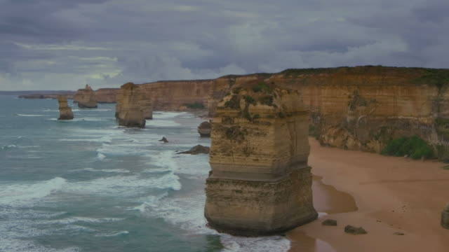 ws zo t/l shot of twelve apostles battered by waves and stormy clouds billowing / port campbell, victoria, australia - naturwunder stock-videos und b-roll-filmmaterial