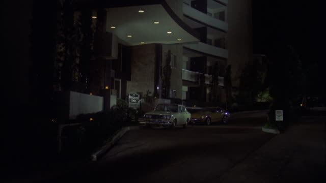 ms tu td shot of twelve story apartment building with lighted entrance and / los angeles, california, united states - anno 1973 video stock e b–roll