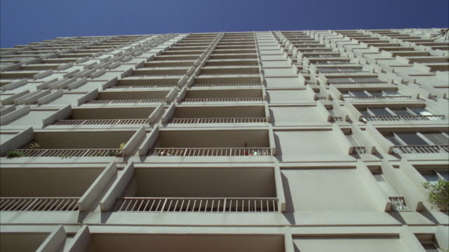 MS POV Shot of Twenty Story white concrete apartment building with balconies
