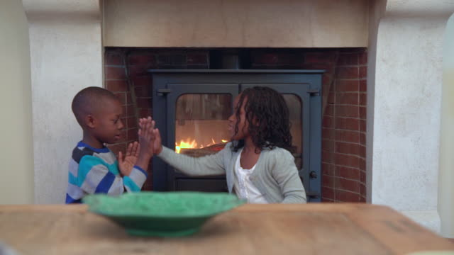ms zi zo shot of two african children playing handclapping game by fireplace / cape town, western cape, south africa - jumper stock videos and b-roll footage