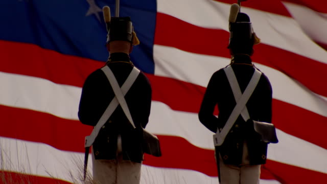 ms tu shot of two american soldiers stand guard with their backs to star spangled banner is lowered at fort mchenry / baltimore, maryland, united states  - gun stock videos and b-roll footage