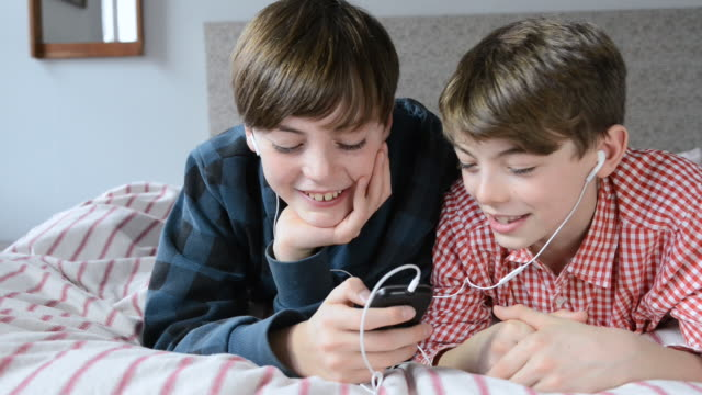 MS Shot of two boys in bedroom texting on mobile phone / London, Greater London, United Kingdom