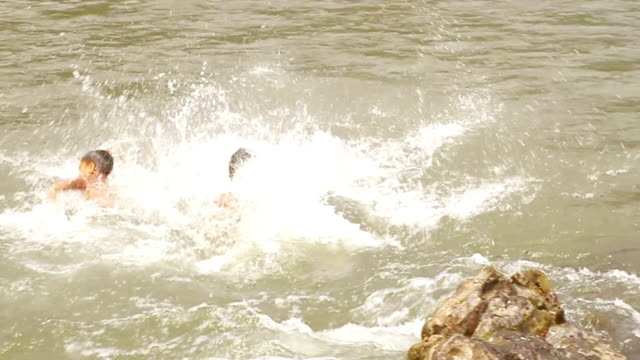 MS TS SLO MO Shot of two boys jumping into water with jeery cans / Ou river, Luang Prabang, Laos