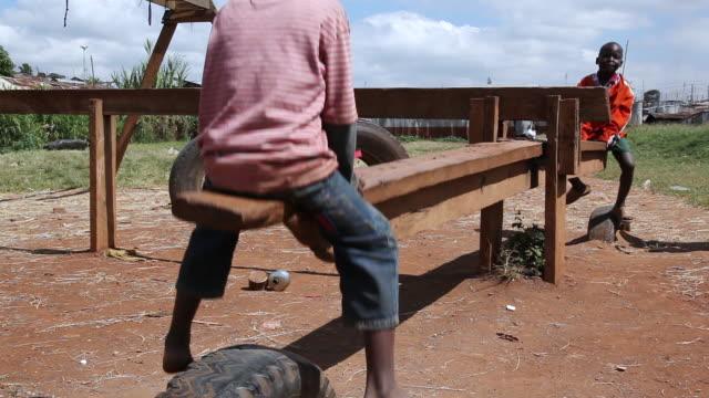 vídeos y material grabado en eventos de stock de ms shot of two boys playing in makeshift seesaw made of pieces of wood and old tires in kibera slum / nairobi, kenya - balancín