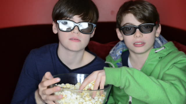 MS Shot of two boys with 3D glasses eating popcorn / London, Greater London, United Kingdom