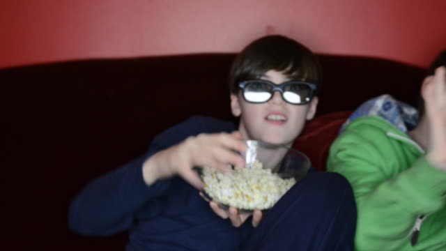 vídeos de stock, filmes e b-roll de ms shot of two boys with 3d glasses eating popcorn / london, greater london, united kingdom - óculos de terceira dimensão