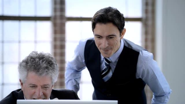 Schot van twee zakenman praten over een monitor