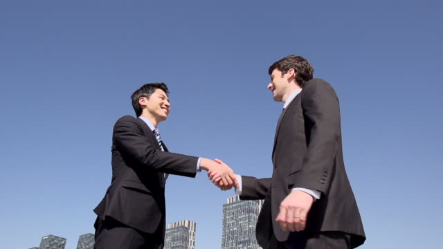 MS SLO MO Shot of two Businessmen shaking hands / Incheon, South Korea