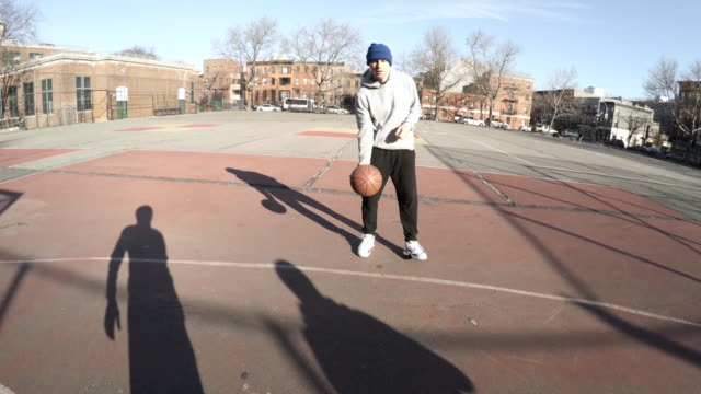 POV shot of two candid, young men in their twenties playing basketball - 4k