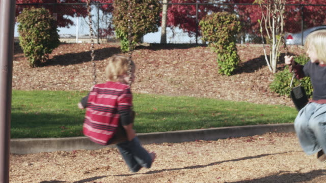 vídeos y material grabado en eventos de stock de ms slo mo shot of two children swing together on warm sunny day / beaverton, oregon, united states - columpiarse