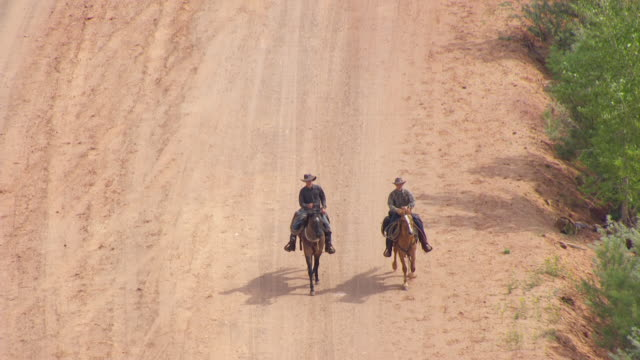 MS AERIAL TS Shot of two cowboys riding on horses / Hildale, Utah, United States