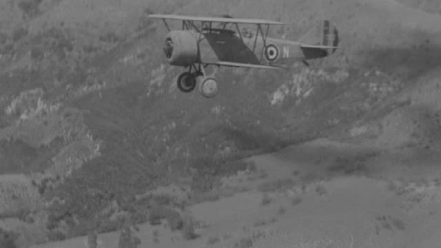 ms aerial shot of two fighter planes flying side by side from right to left over mountain range - 複葉機点の映像素材/bロール
