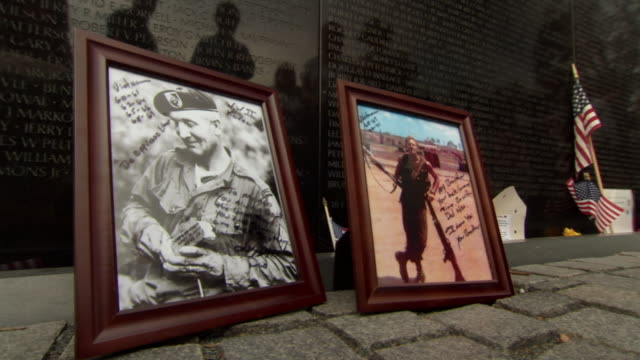 MS Shot of two frame pictures of soldiers left at Vietnam Veterans Memorial Wall / Washington, District of Columbia, United States