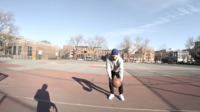 POV shot of two friends play basketball at a local court in Brooklyn, NYC - 4k