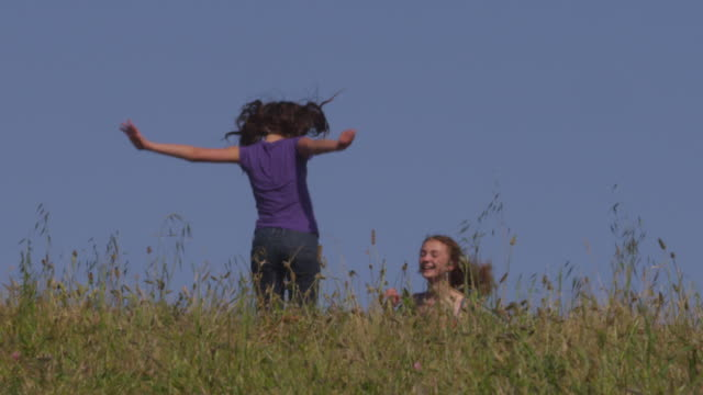 ms slo mo  shot of two girls jumping on trampoline hidden in field / santa cruz, california, united states - santa cruz california stock videos and b-roll footage
