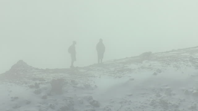 MS AERIAL Shot of two hikers and dog standing on cloudy mist at peak of mount elbert in lake county / Colorado, United States