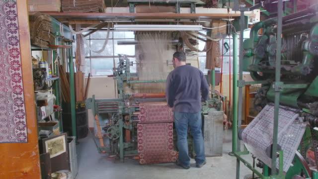 ws pan shot of two jacquard looms on the floor of textile company / red lion, pennsylvania, united states  - telaio attrezzatura per arti e mestieri video stock e b–roll