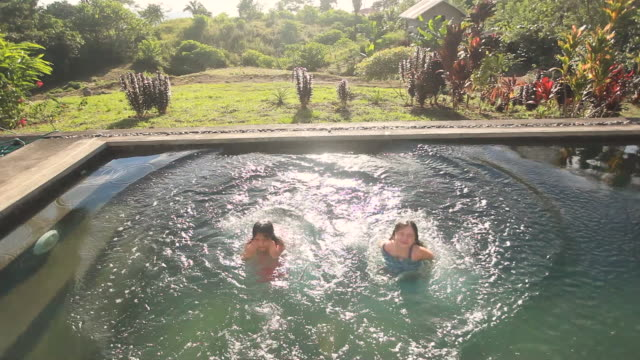 ws shot of two little girls jumping into pool fully clothed in tropical setting / montezuma, punteranes, costa rica - kelly mason videos stock videos & royalty-free footage