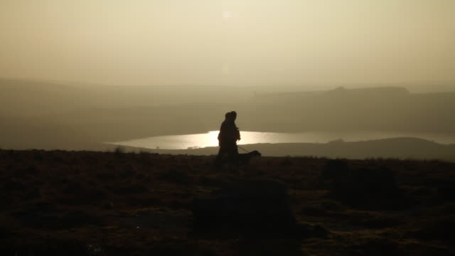 stockvideo's en b-roll-footage met ms shot of two men and dog silhouetted walking in low sun, foggy skies, and hilly landscape / dartmoor, england, united kingdom - wiese
