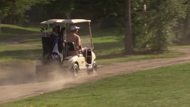 ms ts zo shot of two men driving away in golf cart / fairbanks, alaska, united states - golf cart stock videos and b-roll footage