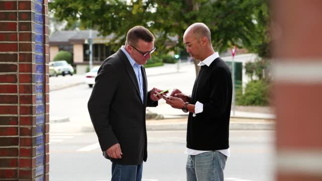 MS Shot of two men exhanging information by bumping smart phones / Santa Cruz, California, United States