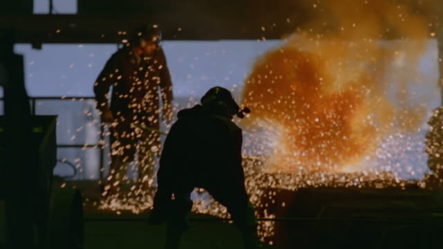 MS SLO MO Shot of Two men in protective gear tending to blast furnace
