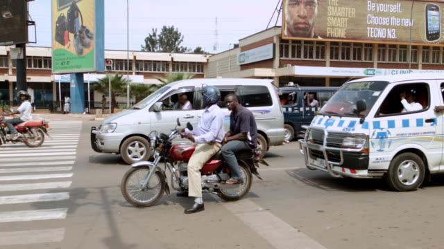 ms ts shot of two men on motorcycle crosses busy intersection / kampala, uganda - kampala stock videos & royalty-free footage