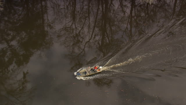 MS AERIAL ZO Shot of two men roaming in boat at Altamaha River and swamp landscape / Georgia, United States