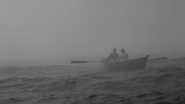 WS Shot of two men sailing fishing boat in ocean