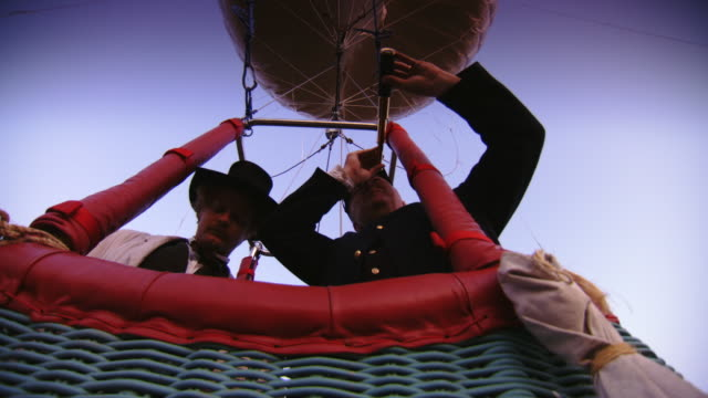 ms pan shot of two men stand in hot air balloon basket one looks through spyglass and other points at distance / rochester, new york, united states - basket stock videos and b-roll footage