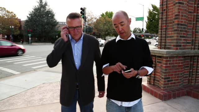 MS TS Shot of two men walking down street and talking while holding smart phone and tablet / Santa Cruz, California, United States