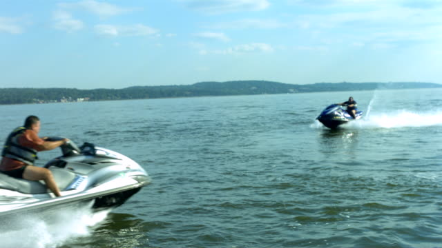ws ts slo mo shot of two men's riding on jet ski / new york, united states - acquascooter video stock e b–roll
