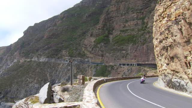 MS PAN Shot of two motorbikes riding along coastal road at Hout Bay / South Africa