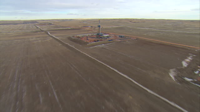 WS AERIAL Shot of two oil drilling rigs in Bakken oil field near Watford City / Watford City, North Dakota, United States