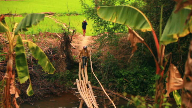 MS Shot of two people crossing small primitive wooden bridge , piece of green rice field / Road from Luang Prabang to Nong Khio, Luang Prabang, Laos