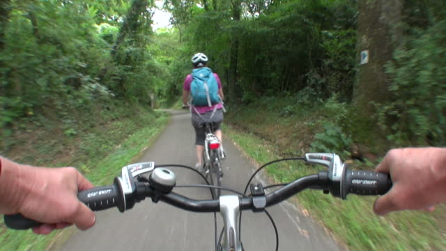 vidéos et rushes de ms pov shot of two people cyclist cycling with cycle helmet through forest area / echternach, luxembourg - grand duché du luxembourg