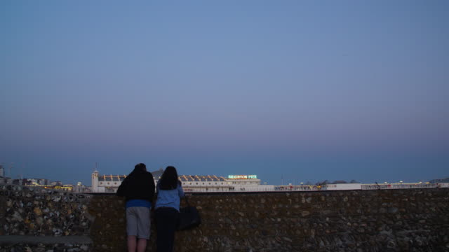 shot of two people leaning against a seawall on brighton beach. - brighton brighton and hove stock-videos und b-roll-filmmaterial